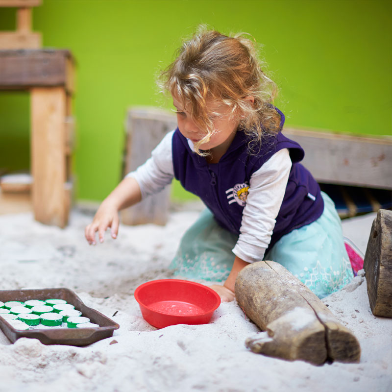 Little girl playing in a sandpit