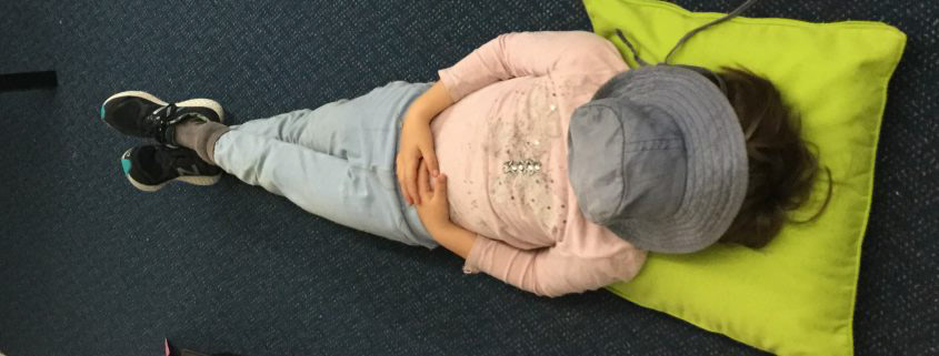 A child lying on the floor doing mindfulness