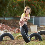 Girl riding a tire hanging from tree