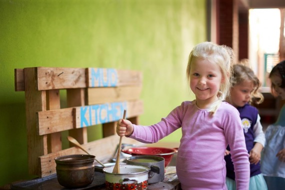kid playing in mud kitchen